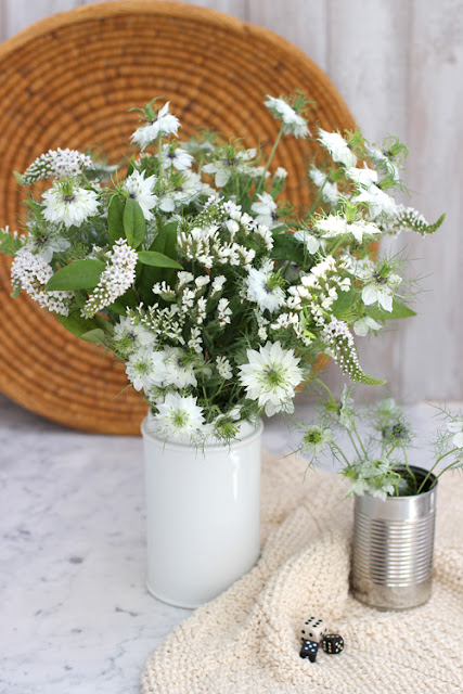 Mixed white late summer flowers in white vintage jar