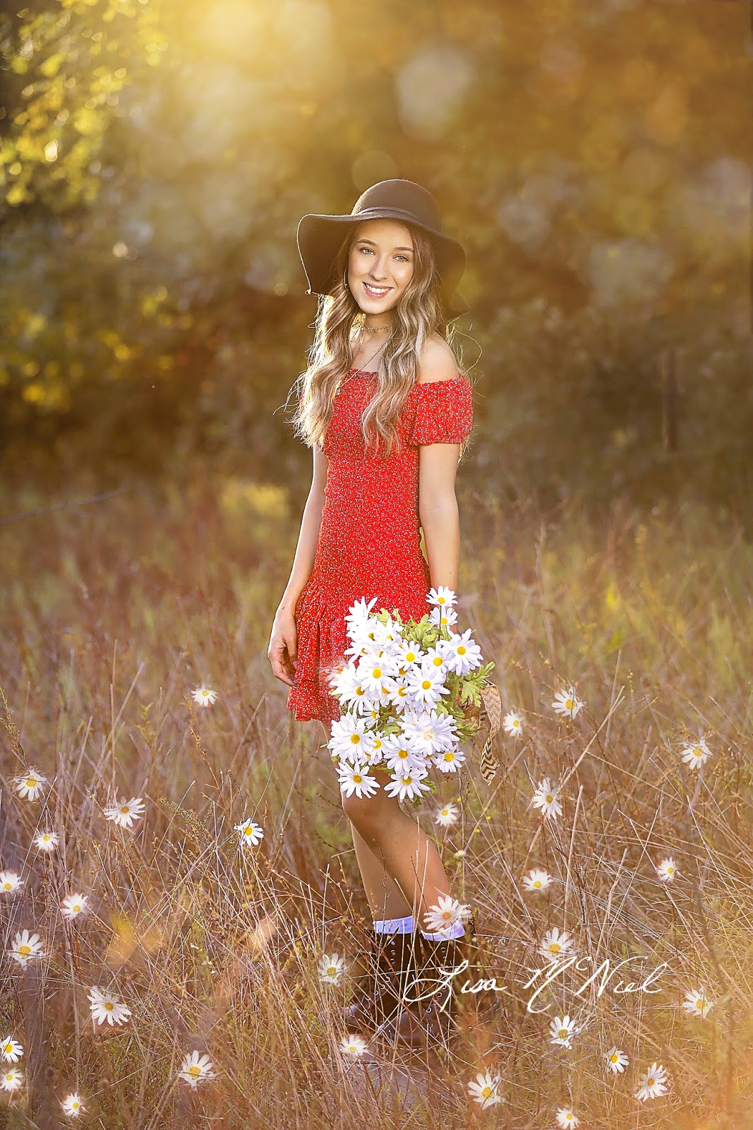cute teen girl holding daisies in field