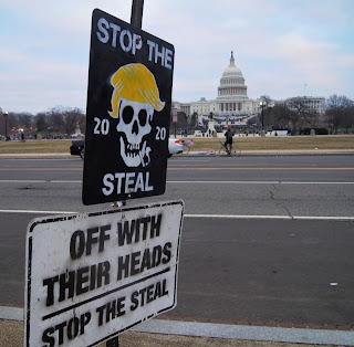 "Signs: ""Stop the 2020 Steal"", ""Off With Their Heads""; US Capitol in background"