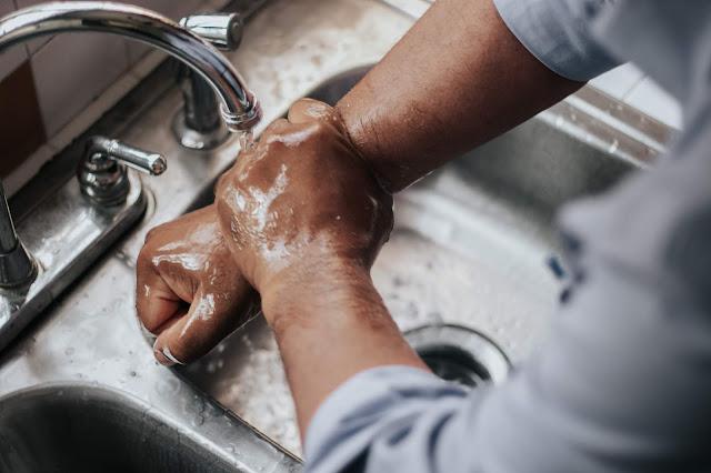 Homem lava mãos na torneira
