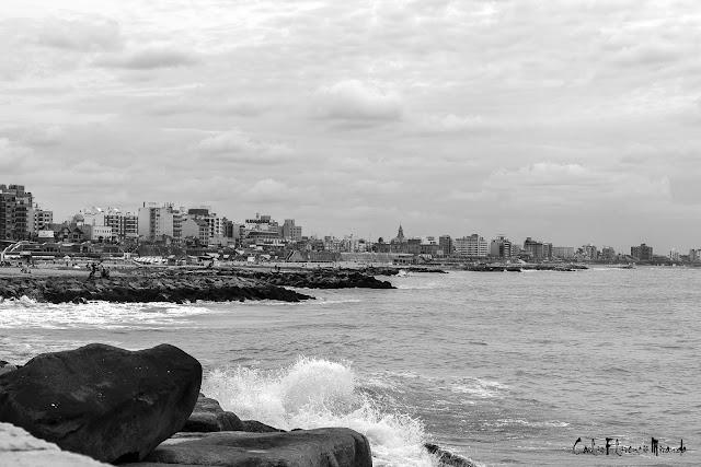 Blanco  Negro.El mar rompiendo contra las rocas y al fondo Mar del Plata.