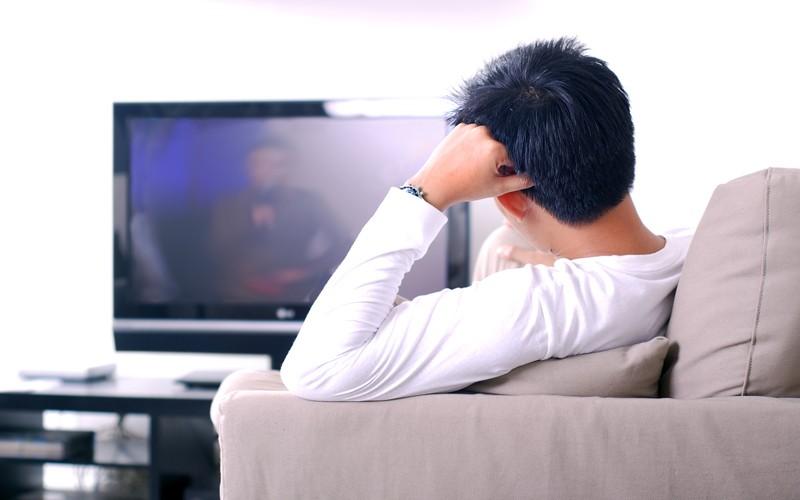 Pessoa cega sentada em uma poltrona assistindo televisão - audiodescrição faz imagens aparecerem em sua mente