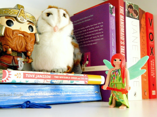 A photo showing a shelf filled with books, and also two figures, a fairy and Gimli from Lord of the Rings, and an owl plush toy