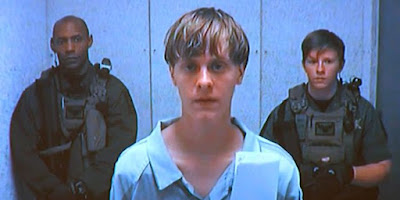 Dylann Roof appeared in court in a video feed from a nearby jail.