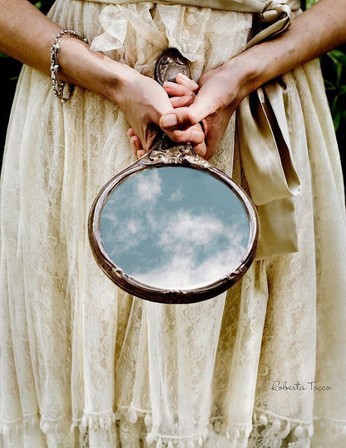 A woman in a cream dress holding a round handmirror that is reflecting the sky - taken by Roberta Tocco