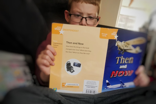 A blonde haired boy, wearing rectangle framed deep blue glasses is reading a ficton book call 'Then and Now' with an old plane and a modern plane on the dark blue cover. The back cover is a pale orange colour with writing on. The boy is sitting on a black sofa. The centre of the image is clear but it blurs as the image moves to the edges.