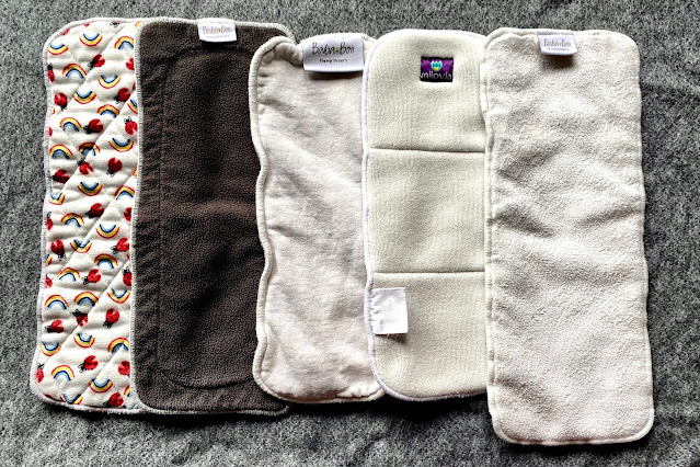 5 different nappy inserts including Bambino Mio polyester with a fun print on, grey charcoal Baba & Boo, Hemp Baba & Boo, Microfibre Milovia and Bamboo Baba & Boo