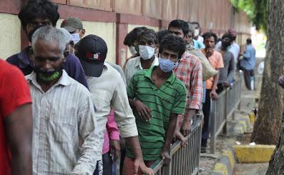 Orang-orang yang memakai masker sebagai tindakan pencegahan terhadap virus corona berbaris untuk menerima makanan gratis yang didistribusikan oleh seorang sukarelawan di Mumbai, India, Rabu, 30 Juni 2021. AP