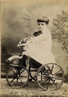 Niño montado en un antiguo triciclo