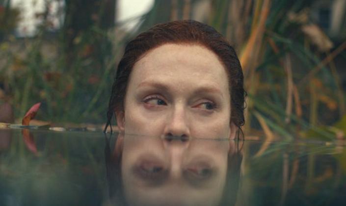 Personagem de Julianne Moore, mulher branca de cerca de 50 anos, ruiva e de olhos azuis, está quase toda submersa num lago, apenas do nariz para cima fora da água que reflete seu rosto. Ela está com olhar apreensivo.