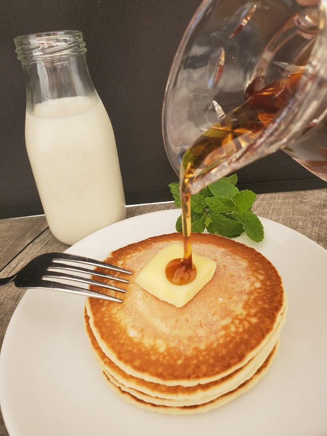 just a plate of hot cakes with butter and syrup on a white plate with a bottle of milk in the background