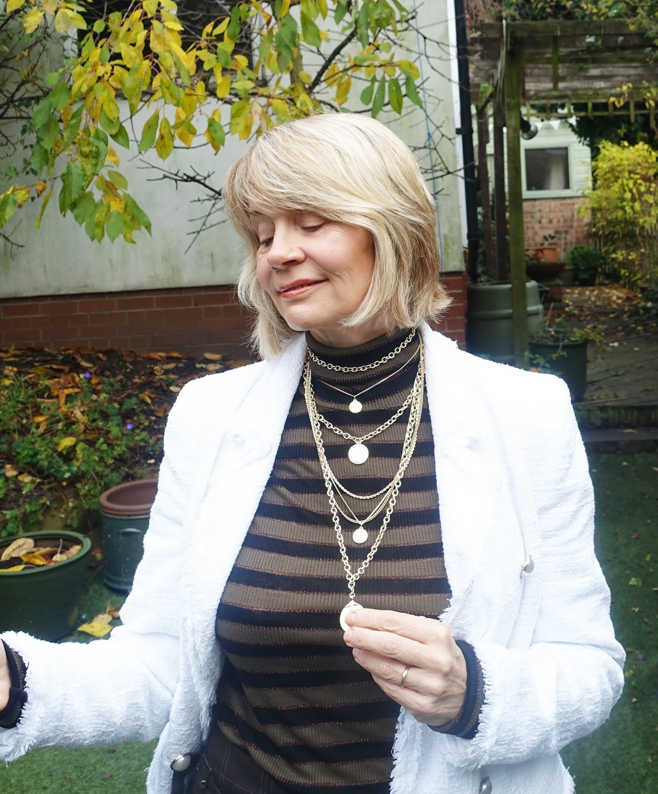 Brown Oxford Bag trousers from the 1990s worn with a mock neck lurex striped jumper, white jacket and layered coin necklace by over-50s style blogger Is This Mutton?