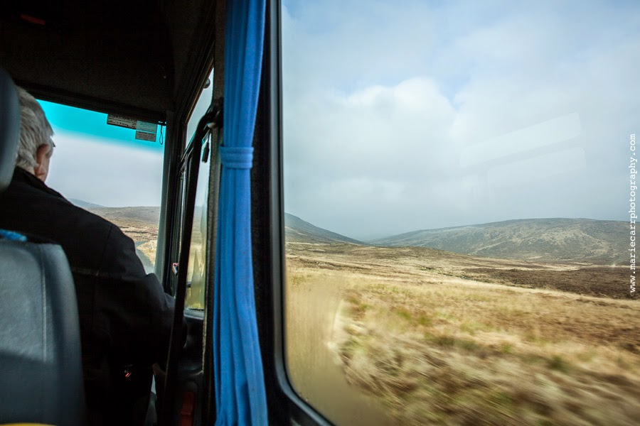Picture of the driver and view outside of the donegal hills, from the passenger seat on a bus