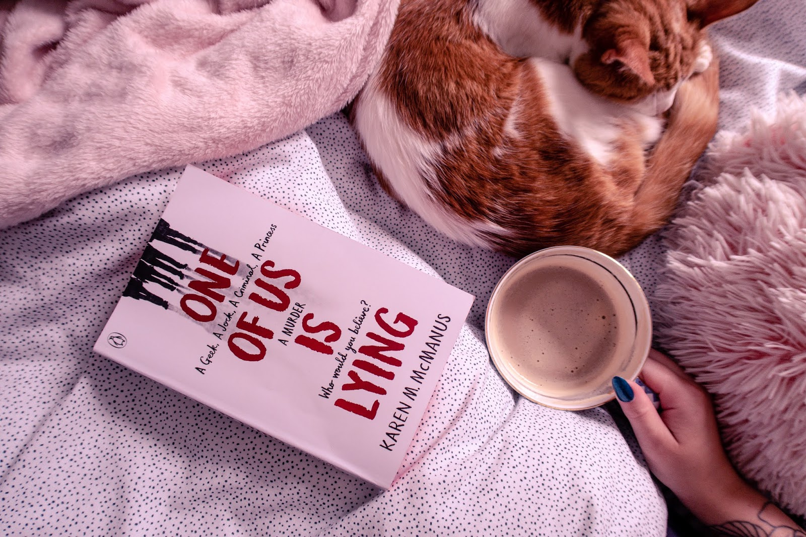 Birds eye view of One of us is lying book on a bed with spotted bedding and a cat to the right with a cup of coffee next to it