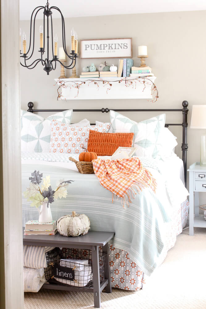 chandelier, shelf above bed with books and pumpkins, orange and blue bedding