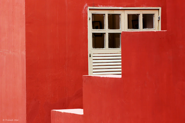 White Window partially visible behind the Red Zig Zag Side Rail of a Staircase at Jawahar Kala Kendra, Art Center in Jaipur, India.