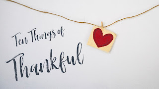 "Photo: A red heart hangs from a wire. ""Ten Things of Thankful"" is written to the left of the heart."
