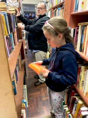 Girls in front of book shelves in second hand bookshop