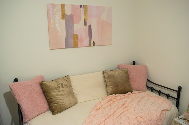 Pink, gold and grey canvas above a black day bed dressed in pink, cream and bronze bedding.