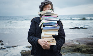 Liz Treacher by the sea carrying a pile of books