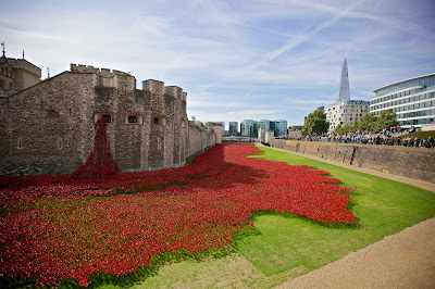 Tower of London moat with red ceramic poppies spilling out and onto the grass.