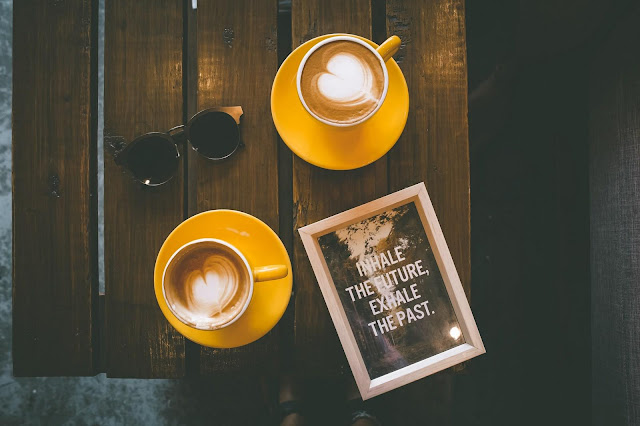 Two Lattes in Yellow Cups with Saucers on Brown Wooden Table | Photo by Toa Heftiba via Unsplash.com