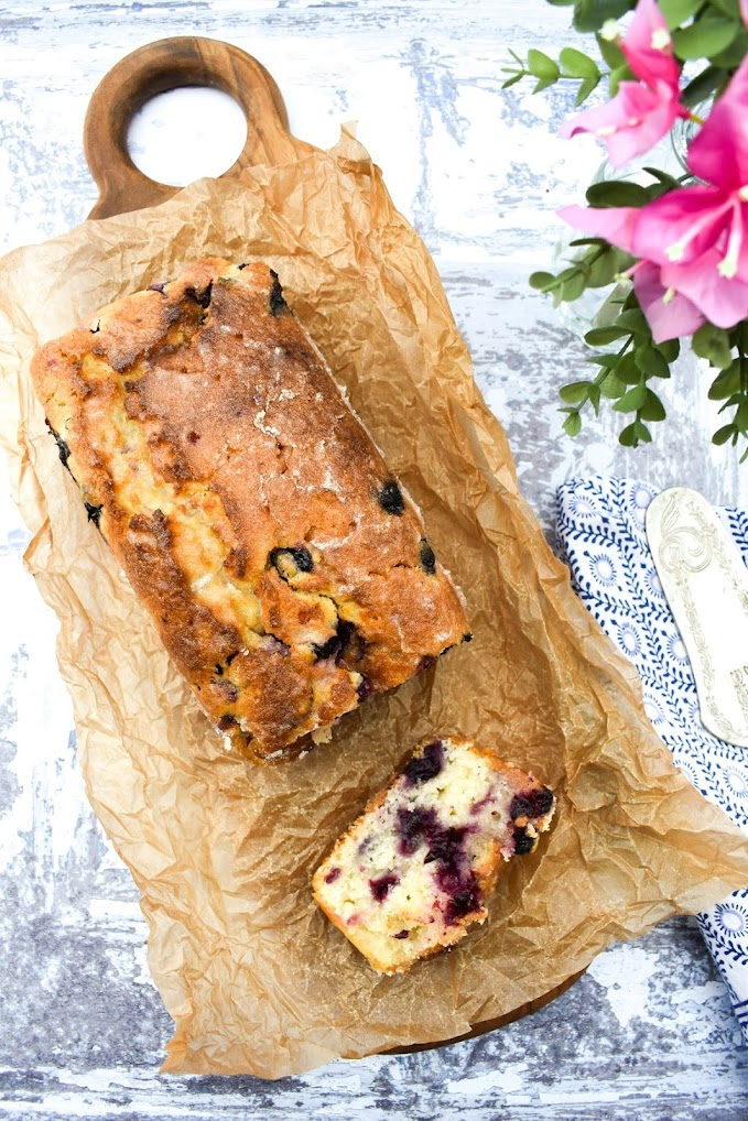 Sliced blueberry lemon cake on a wooden platter topped with baking paper