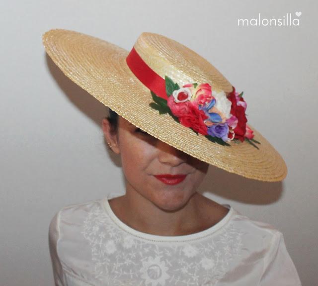 Chica posando de frente con pamela de paja trenzada, flores y cinta en rojo y blusa blanca