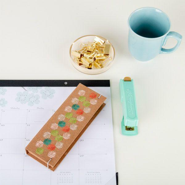 rectangular kraft box with colorful embroidered leaf design on desk