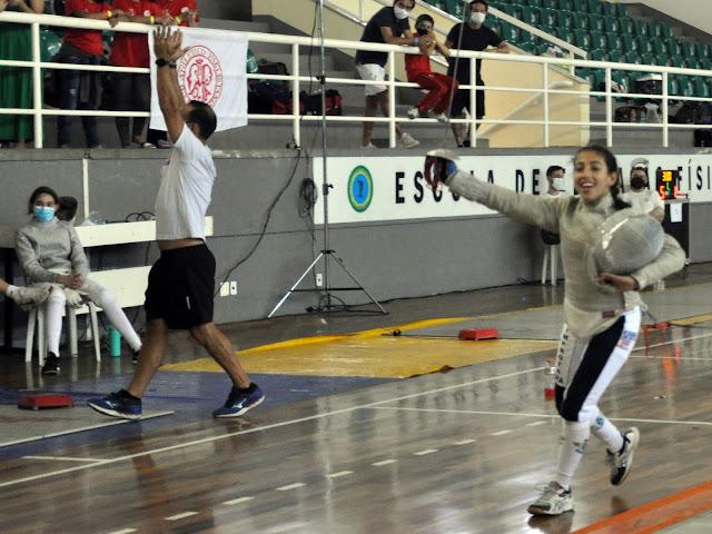 Júlia Improta corre em pista comemorando e técnico ao fundo levanta os braços