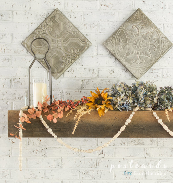 fireplace mantel with flowers, vintage ceiling tins, and lanterns with wood bead garland