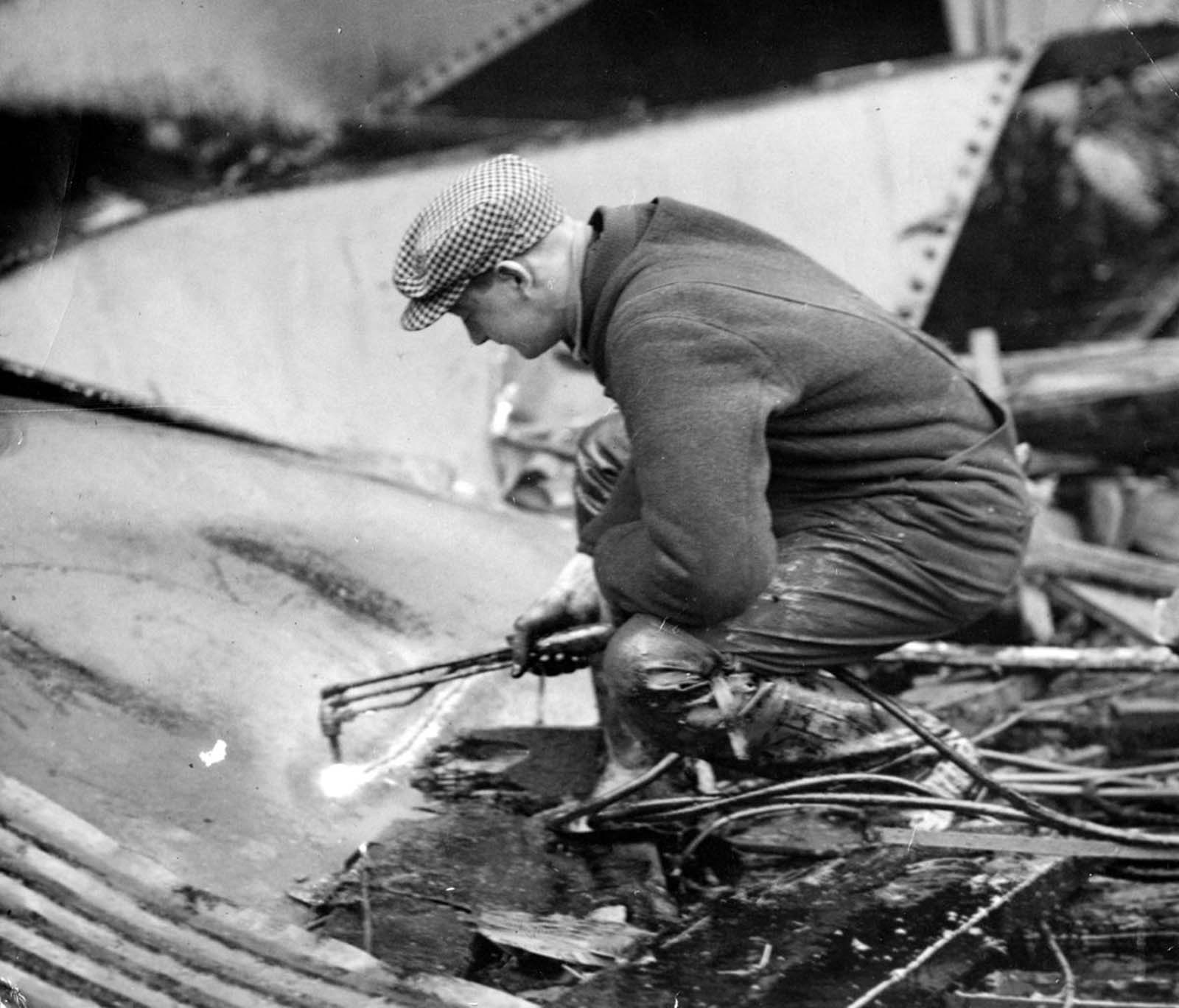 "Welders carefully began cutting up the molasses tank with torches in the search for bodies on Jan. 20, 1919, five days after the Great Molasses Flood in Boston's North End. Even though firemen constantly sprayed water on the twisted wreckage, it wasn't until the city ordered powerful streams from its fireboat that the molasses began to dissipate. The salt water of the harbor ""cut"" the molasses and eventually the welders could see the structure of the original tank."