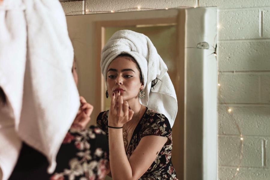 Frau schminkt sich vor dem Badezimmerspiegel
