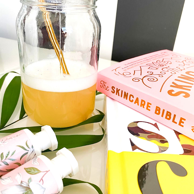 Aesthetically pleasing image of skincare books, products with a collagen beauty drink