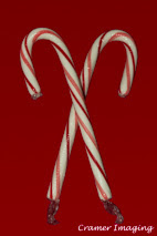 Cramer Imaging's professional quality holiday or Christmas product photograph of two crossed candy canes on a red background