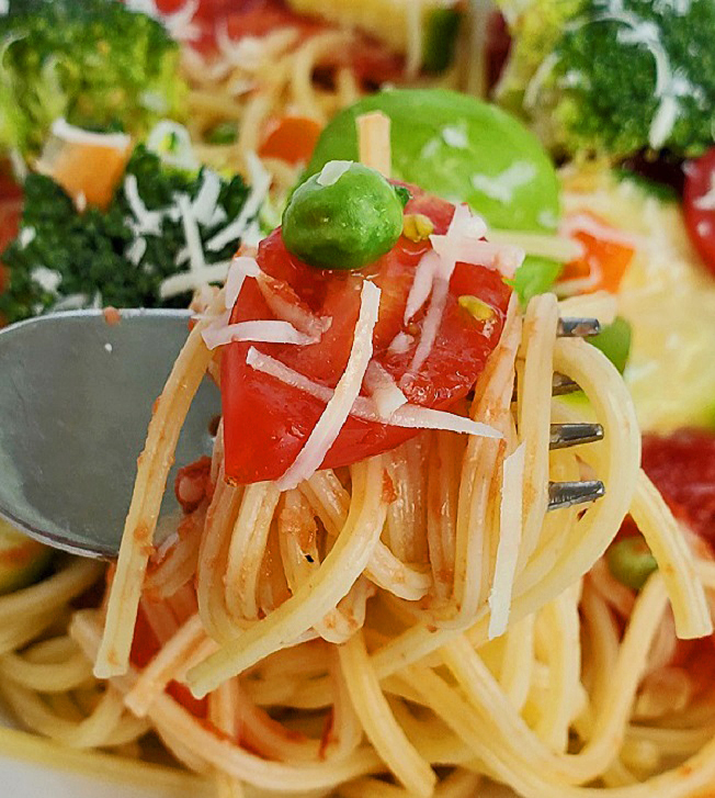 this is a close up photo of spaghetti and fresh vegetables on top with romano cheese grated on it