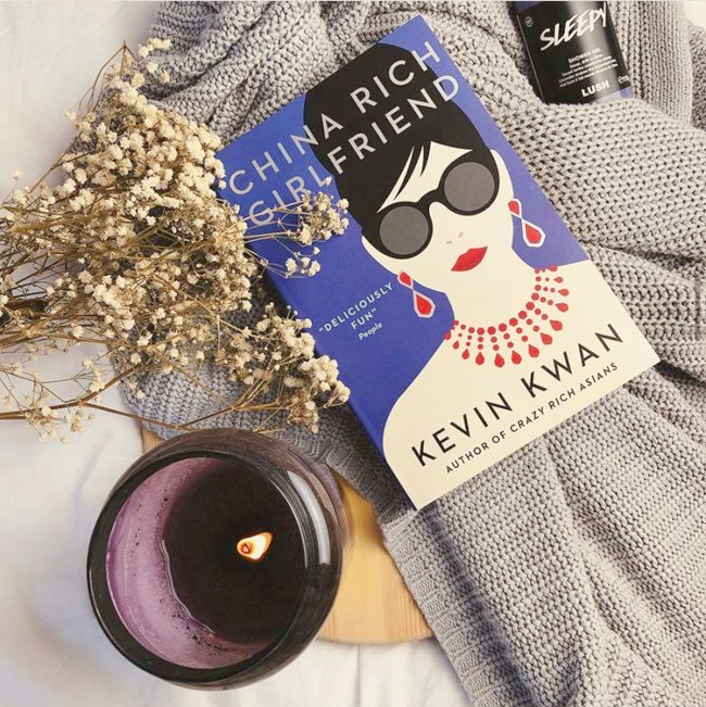 Cover of 'CHina Rich Girlfriend' by Kevin Kwan next to a purple candle and baby's breath and on a grey cardigan