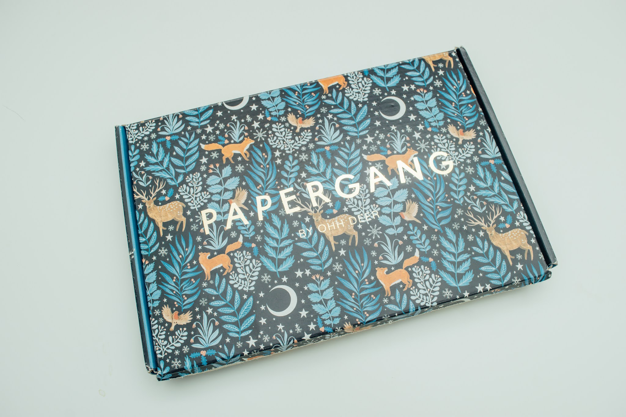 A navy box with a floral and leafy blue design with fox illustrations