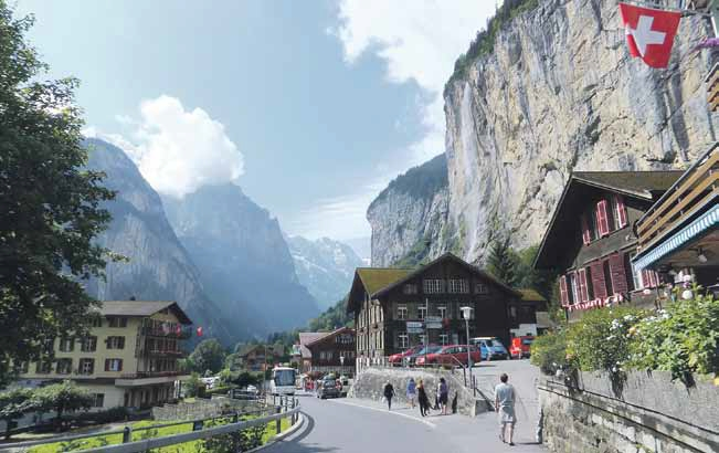 The tall majestic cliffs and Staubbach Falls (on the right) greet tourists at the Lauterbrunnen Valley.