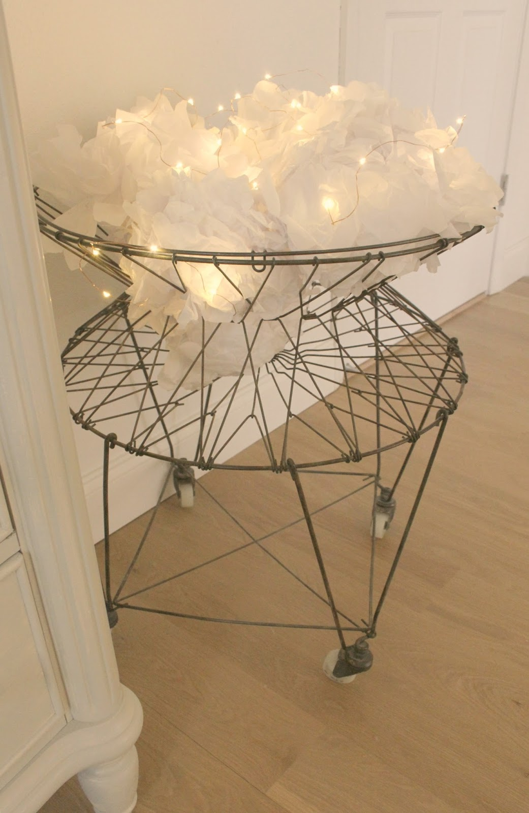 Vintage French wire laundry basket with white tissue poufs and fairy lights