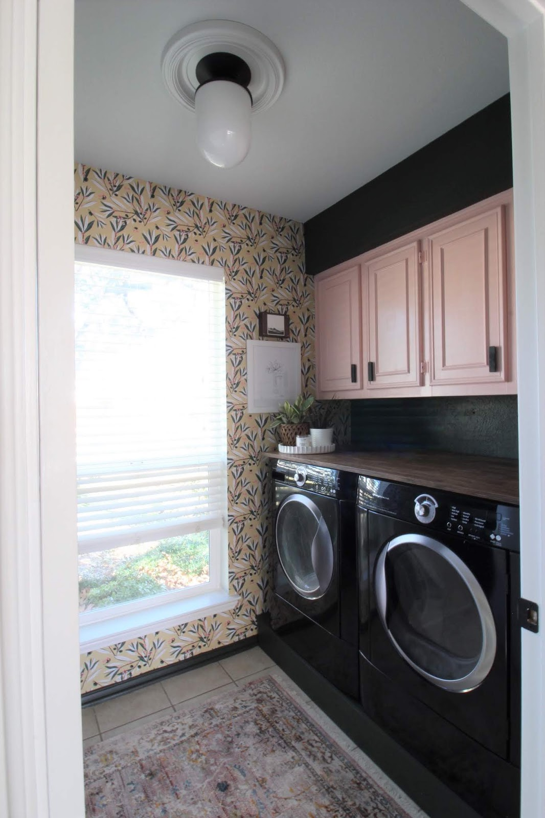 We've lived in our house a whole year!! Check out the tour and a round up of projects I've done. It's been great! | House Homemade wallpapered laundry pink cabinets