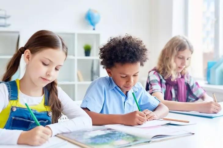 Crianças escrevendo em um caderno na escola