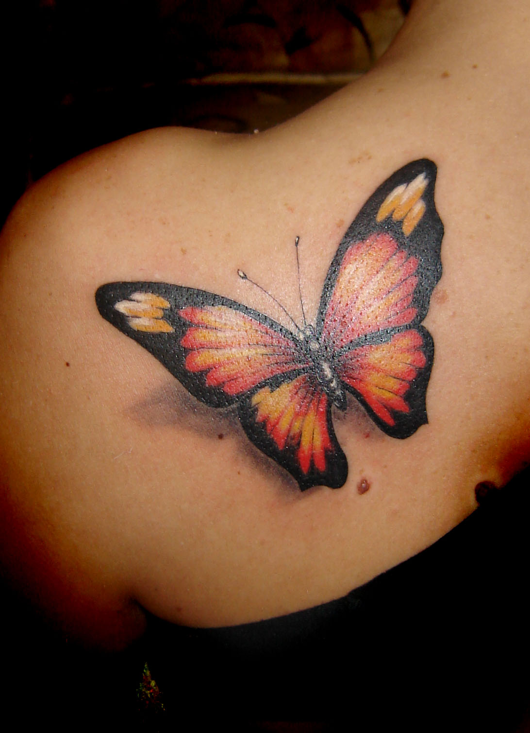 orange erfly tattoo on the shoulder