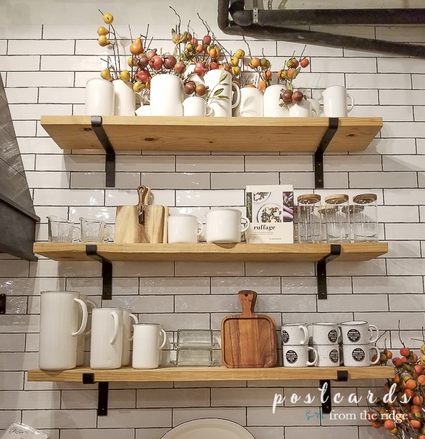 open wood shelves with kitchen items on white subway tiled wall