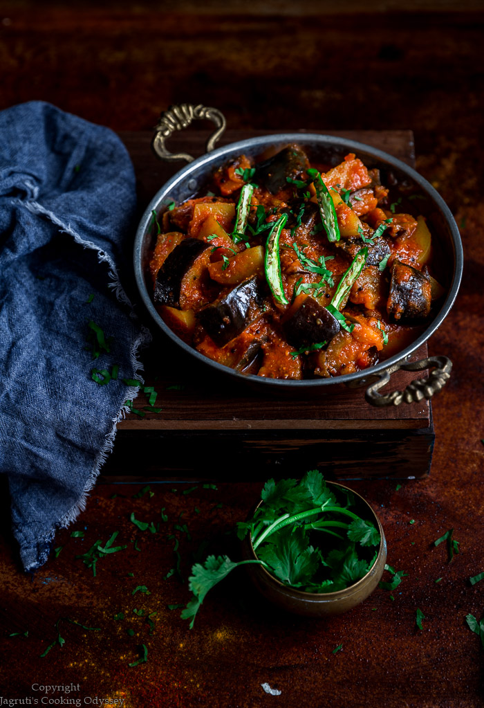 Aubergine and potato curry served in a bowl topped with coriander and slit green chillies on a brown backdrop with spoon