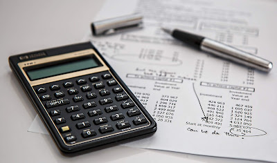 A calculator and pen on a piece of paper showing a budget