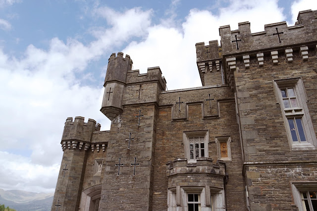 wray castle with bright blue sky and big clouds behind it