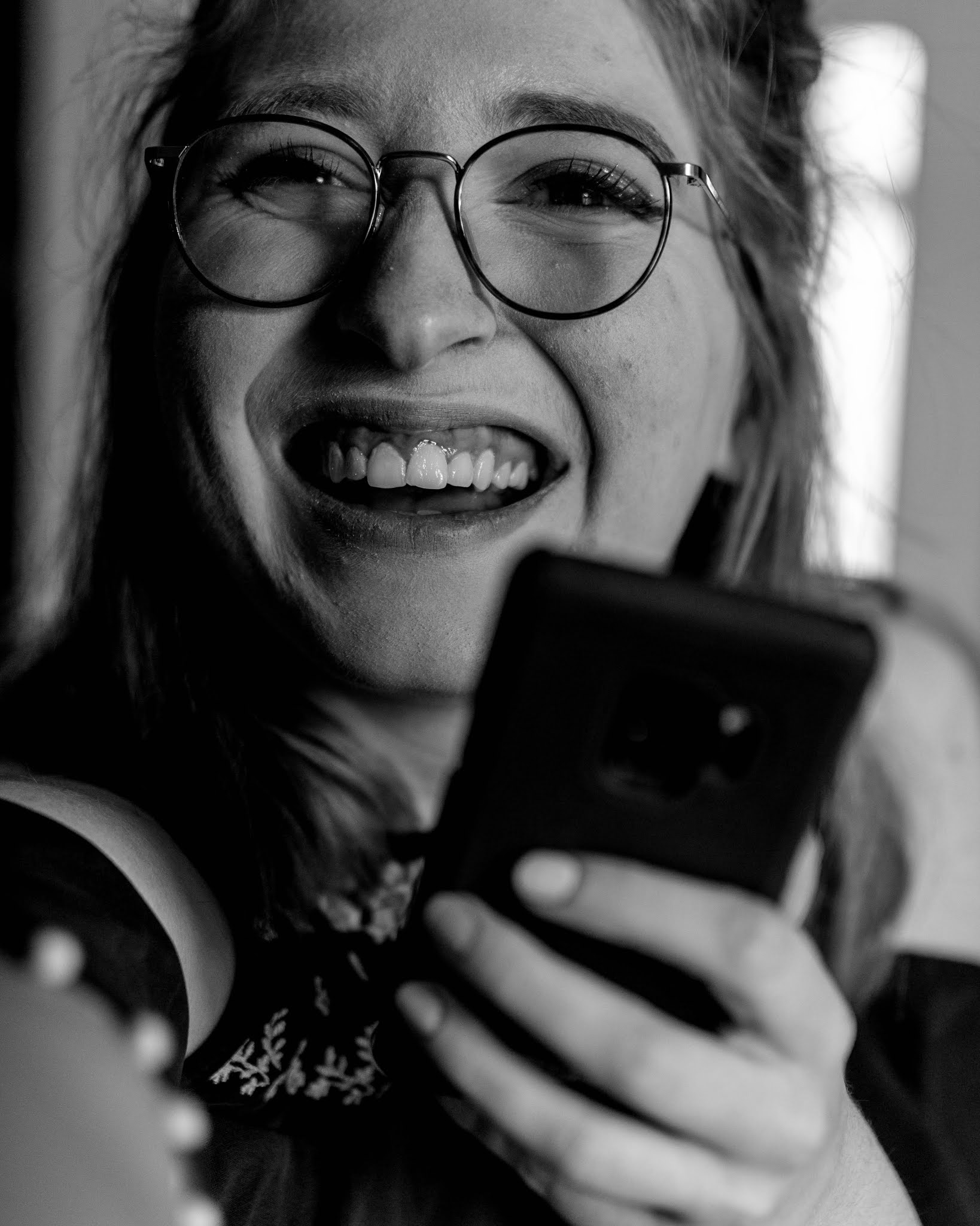 black and white image of girl smiling and holding phone