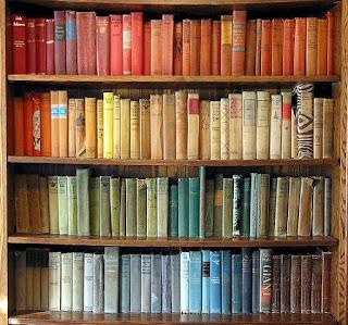 A bookshelf containing books arranged by colour