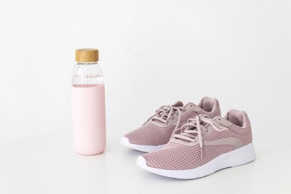Garrafa de água ao lado de um tênis rosa em fundo branco